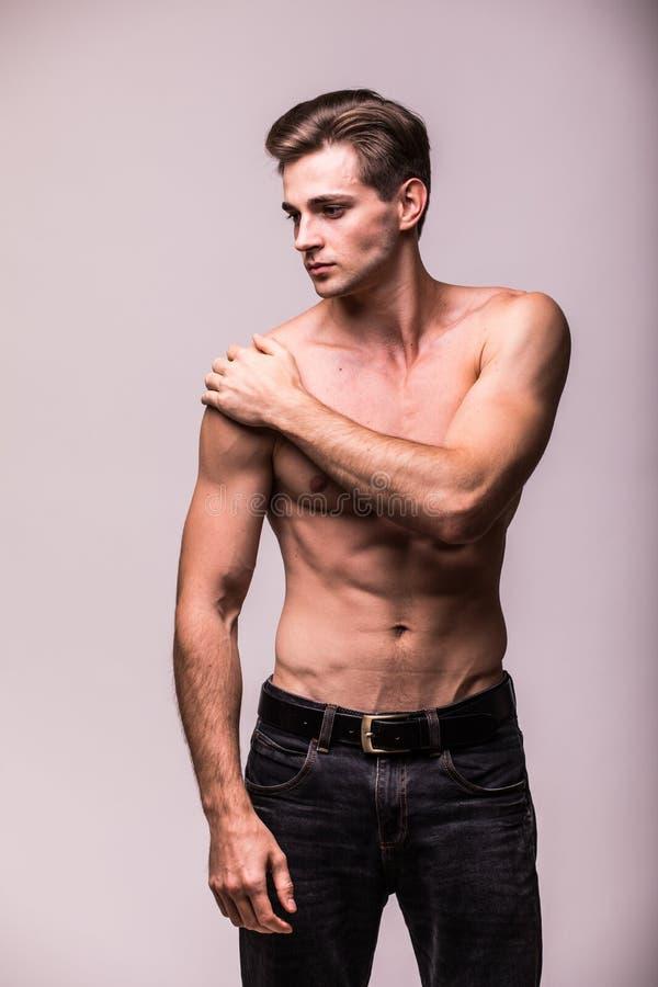 Junger Mann, der unter den Schmerz in seiner Schulter auf grauem Hintergrund leidet lizenzfreies stockfoto