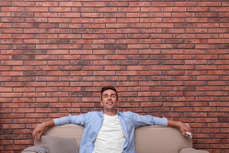 Junger Mann, der unter Klimaanlage sich entspannt stockfotografie