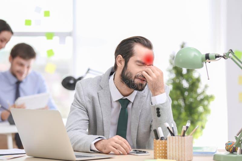 Junger Mann, der unter Kopfschmerzen leidet stockfotos