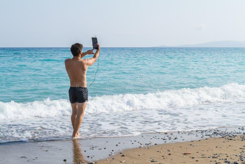 Junger Mann, der unter Verwendung der Kopfhörer und der Tablette am Strand in Verbindung steht lizenzfreie stockfotografie