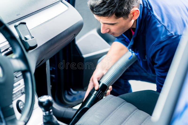 Junger Mann, der Vakuum für das Säubern des Innenraums eines Autos verwendet lizenzfreie stockfotos