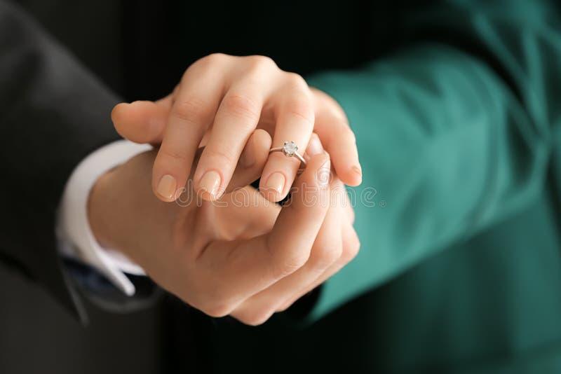 Junger Mann, der Verlobungsring auf Verlobtes \ 's-Finger, Nahaufnahme setzt lizenzfreie stockbilder