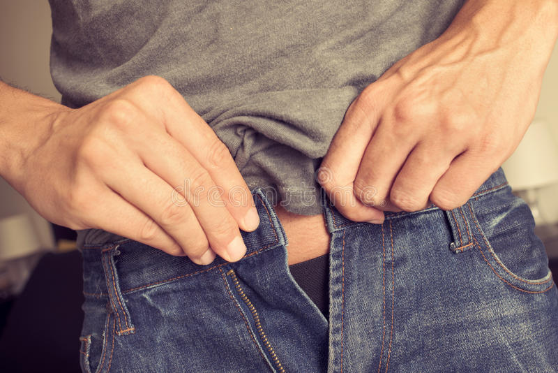 Junger Mann, der versucht, seine Hose zu befestigen lizenzfreies stockbild