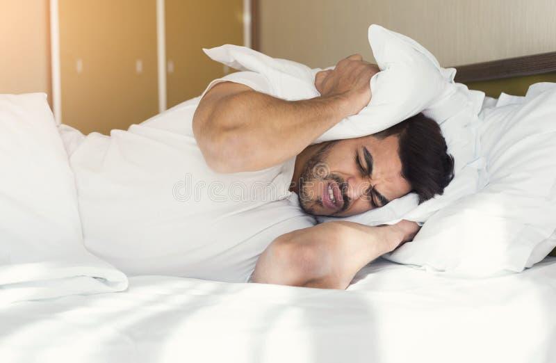 Junger Mann, der versucht, zu schlafen Bedeckungsohren mit Kissen lizenzfreie stockbilder