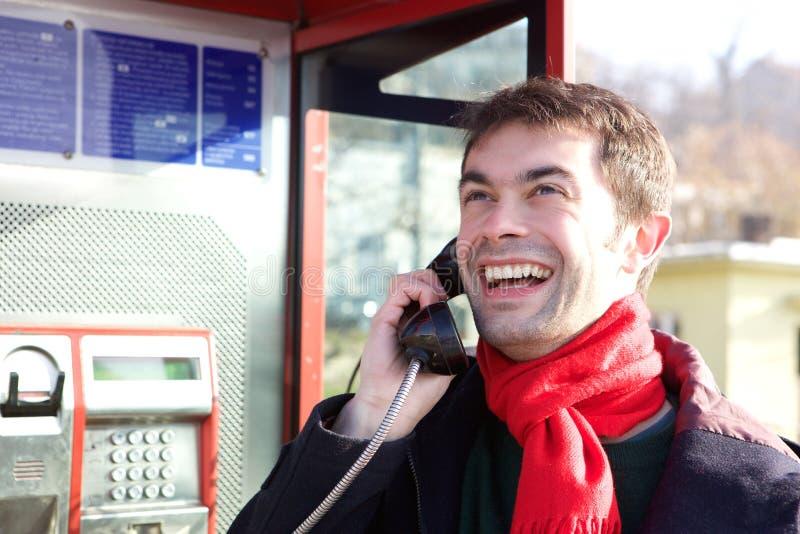 Junger Mann, der von der Telefonzelle nennt lizenzfreie stockfotos