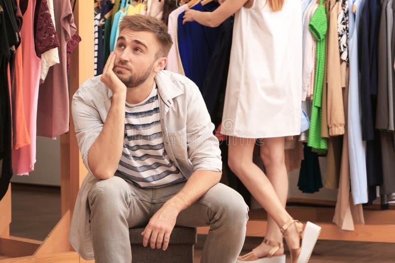 Junger Mann, der während seine Freundin wählt Kleidung wartet stockfoto