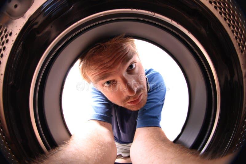 Junger Mann in der Wäschemaschine stockbilder
