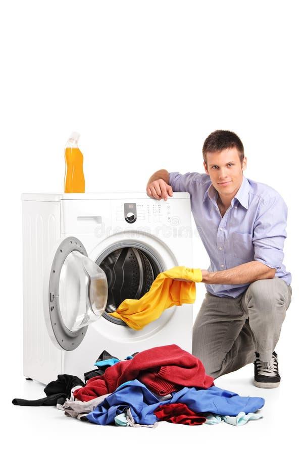 Junger Mann, der Wäscherei tut stockbilder