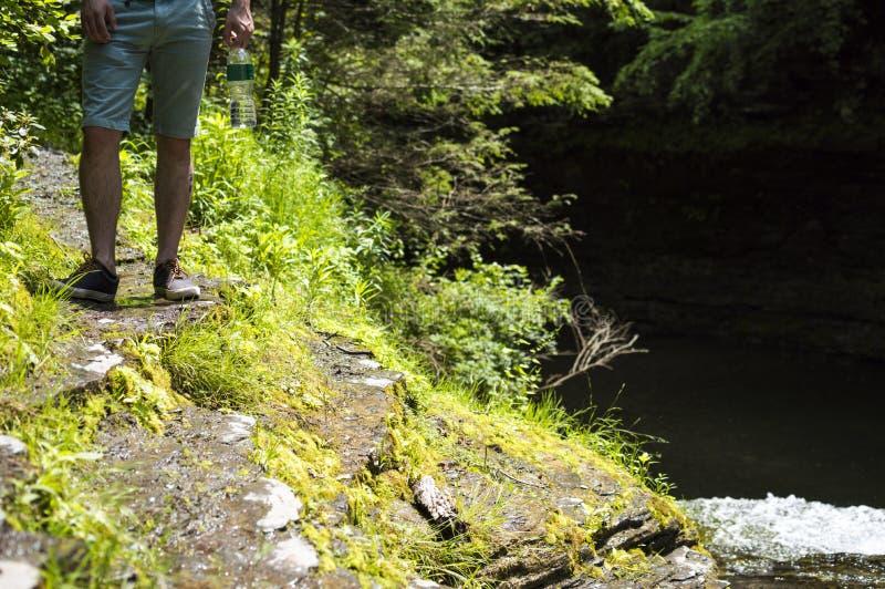 Junger Mann, der Wasserflasche auf Flussufer steht und hält lizenzfreies stockfoto