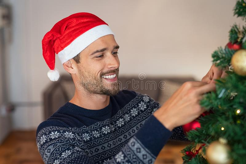 Junger Mann, der Weihnachtsbaum verziert lizenzfreie stockbilder