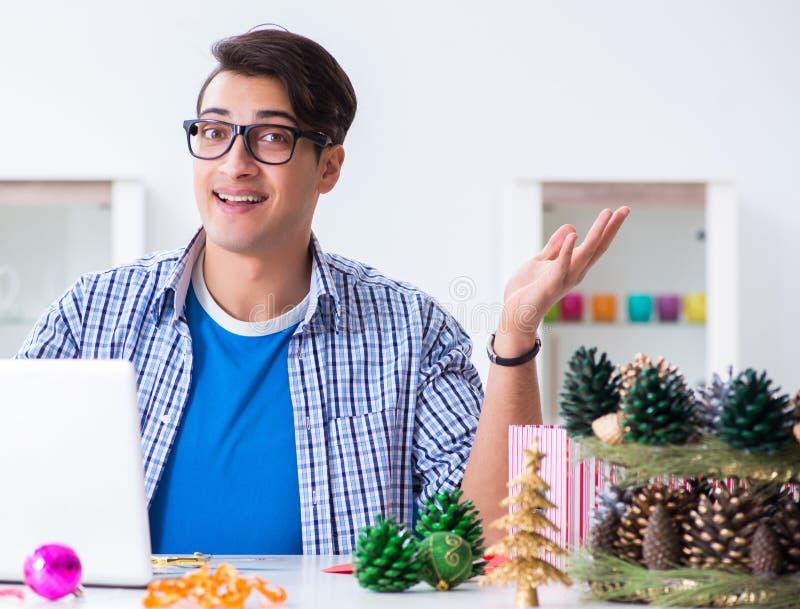 Junger Mann, der Weihnachtsdekoration von den Kegeln macht stockbilder