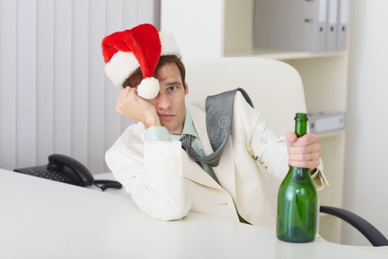 Junger Mann in der Weihnachtshutschutzkappe mit Flasche lizenzfreies stockbild