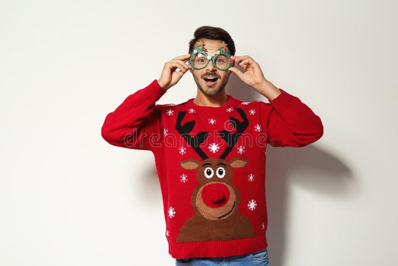 Junger Mann in der Weihnachtsstrickjacke mit Parteigläsern lizenzfreie stockfotos