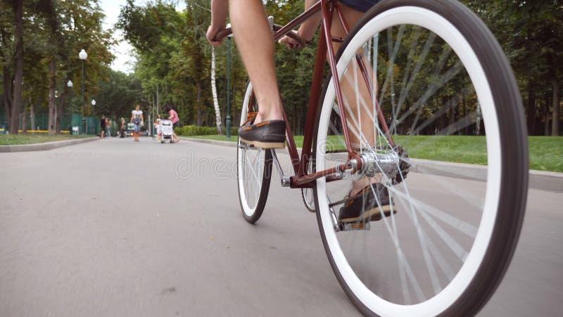 Junger Mann, der Weinlesefahrrad an der Parkstraße fährt Sportliches Kerlradfahren im Freien Gesunder aktiver Lebensstil Niedrige stockfoto