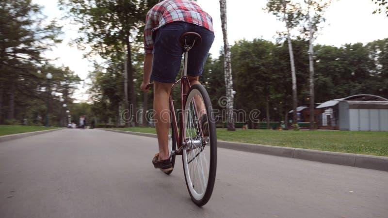Junger Mann, der Weinlesefahrrad an der Parkstraße fährt Sportliches Kerlradfahren im Freien Gesunder aktiver Lebensstil Niedrige stockbilder