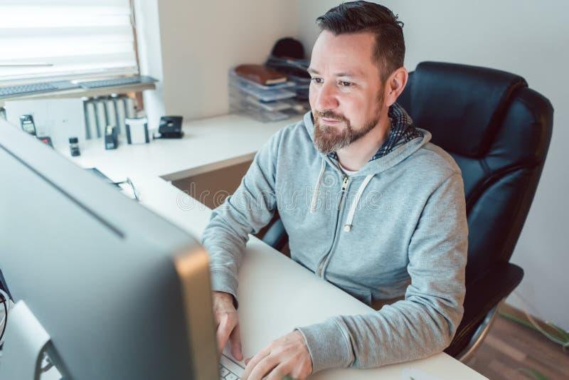 Junger Mann in der Werbeagentur, die auf Computer entwirft stockfotografie