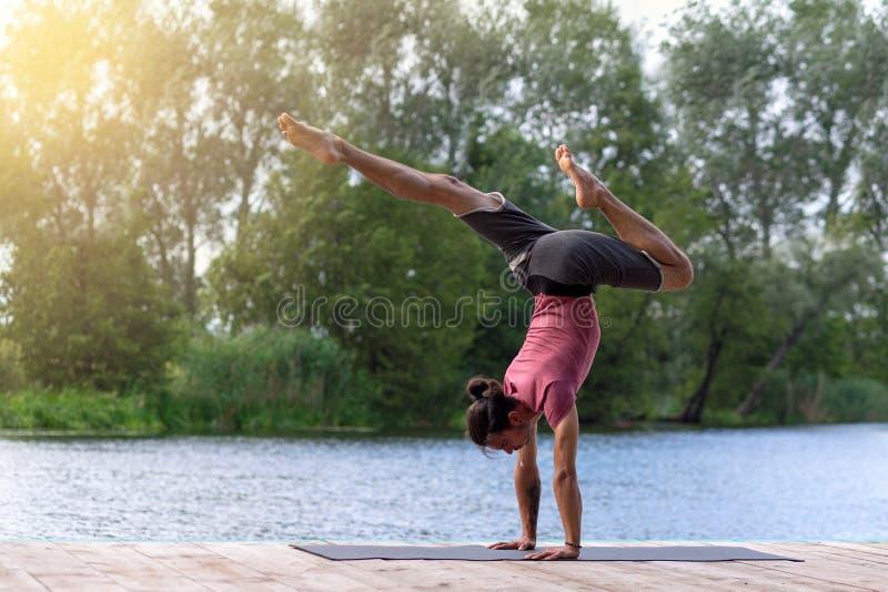 Junger Mann, der Yogaübungen macht Eignung, Sport, Leute und Lebensstilkonzept lizenzfreie stockbilder