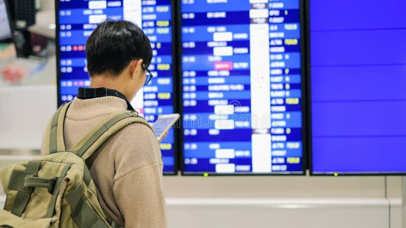 Junger Mann, der Zeitplan über Fluglinienanschlagtafel auf Reise am Flughafen überprüft lizenzfreie stockbilder