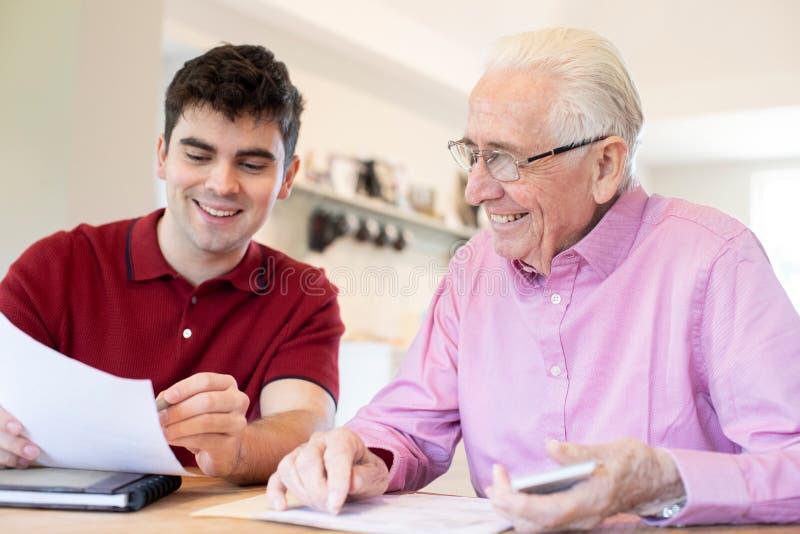 Junger Mann, der zu Hause älterem Nachbar mit Schreibarbeit hilft stockbild