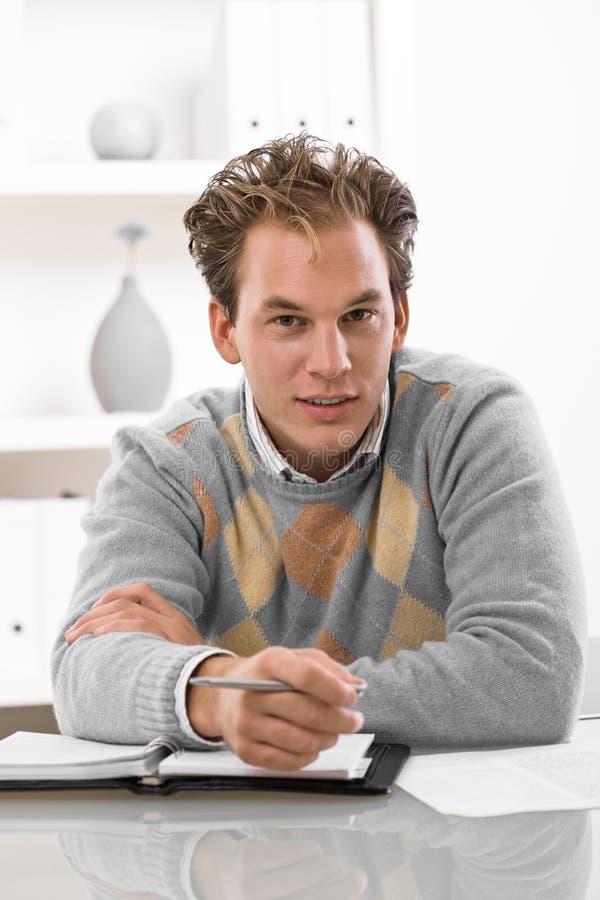 Junger Mann, der zu Hause arbeitet lizenzfreie stockfotos