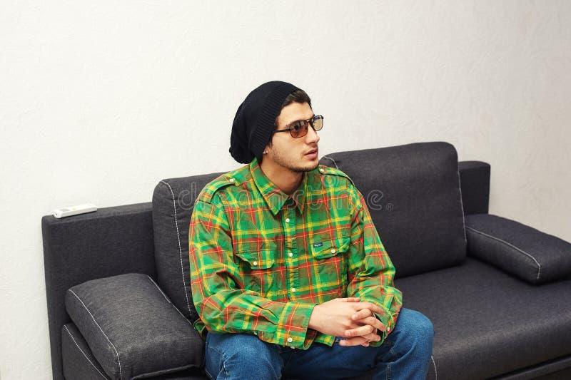 Junger Mann, der zu Hause das Sitzen auf der Couch stillsteht stockbilder