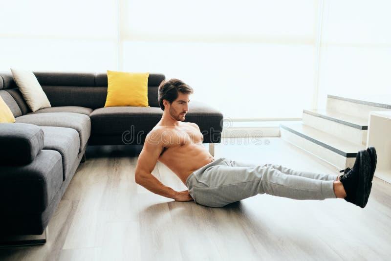 Junger Mann, der zu Hause für gesunden Lebensstil und Eignung ausarbeitet lizenzfreies stockfoto