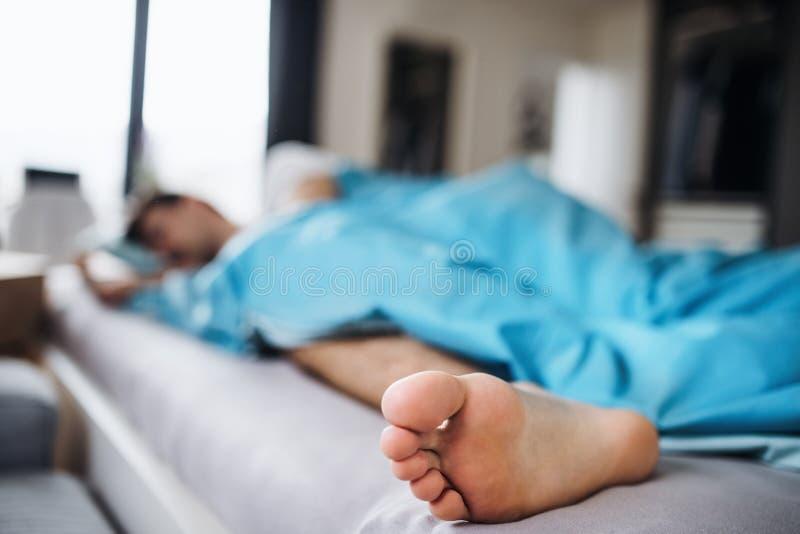 Junger Mann, der zu Hause im Bett, Nahaufnahme des bloßen Fußes schläft lizenzfreie stockfotos