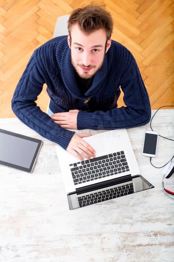 Junger Mann, der zu Hause seine Laptop-Computer verwendet stockfotos