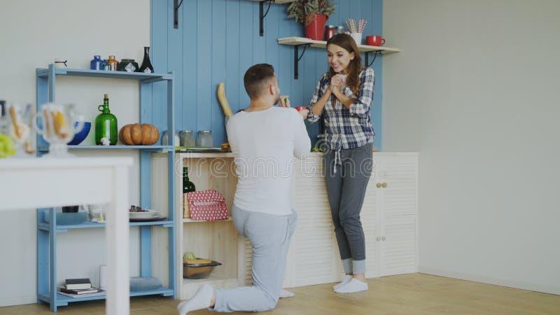 Junger Mann, der zu Hause seiner Freundin in der Küche Antrag macht stockfotografie