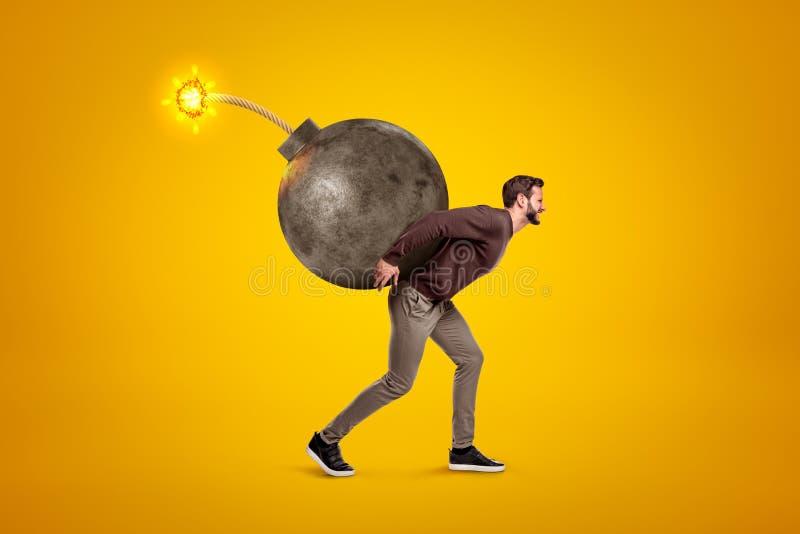Junger Mann in der zufälligen Kleidung, die große Ballbombe mit Sicherung auf seinem zurück auf gelbem Hintergrund trägt lizenzfreies stockfoto