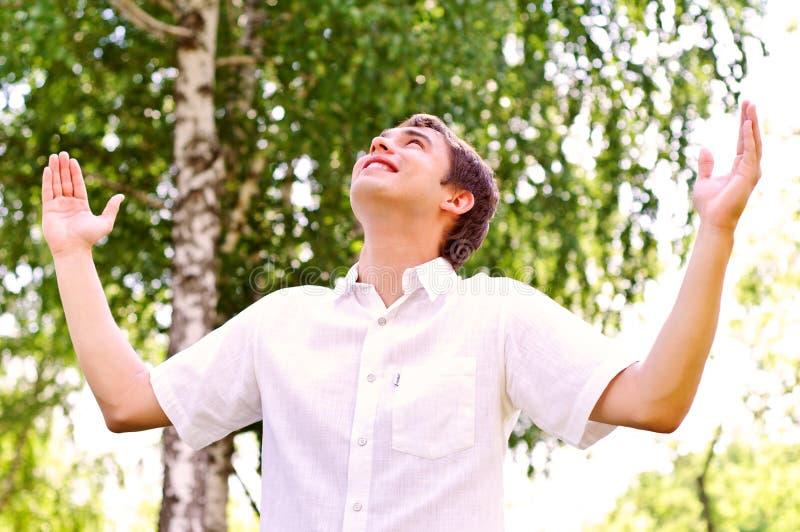 Junger Mann, der zum Himmel, seine Hände hochhalten schaut stockfotografie
