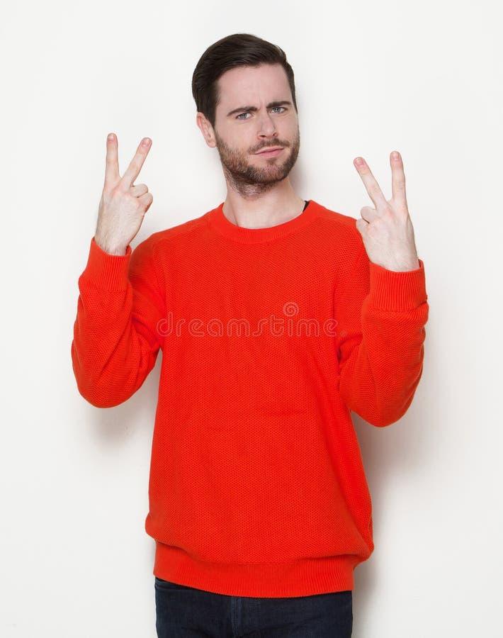 Junger Mann, der zwei Finger zeigt lizenzfreie stockfotografie