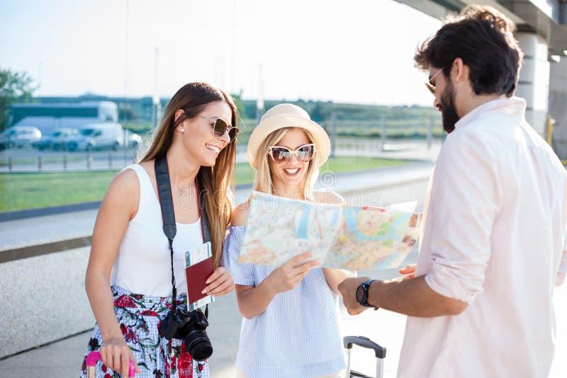 Junger Mann, der zwei schönen jungen weiblichen Touristen Richtungen gibt lizenzfreie stockfotos