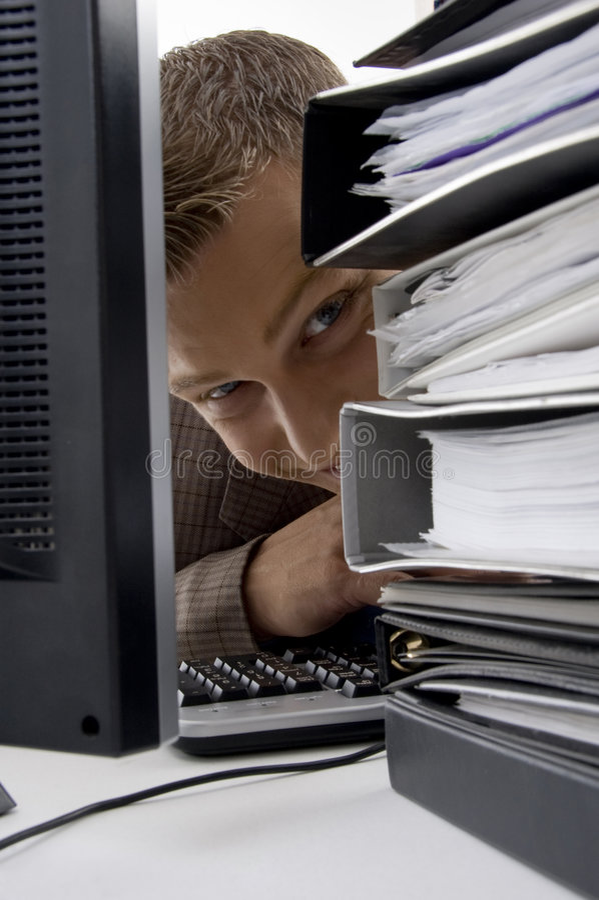 Junger Mann, der zwischen den Dateien und dem Computer schaut stockbilder