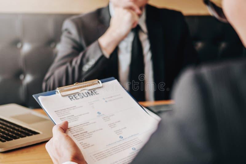 Junger Mann des Angestellten, der über seine Profilzusammenfassung Senior erklärt lizenzfreie stockfotos