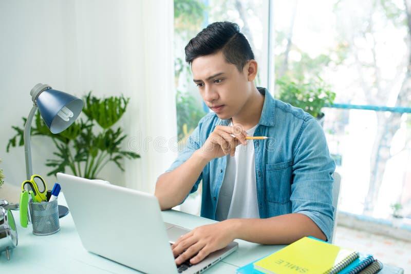 Junger Mann des besorgten Unternehmers, der am Schreibtisch auf dem Laptopschauen arbeitet stockfotografie