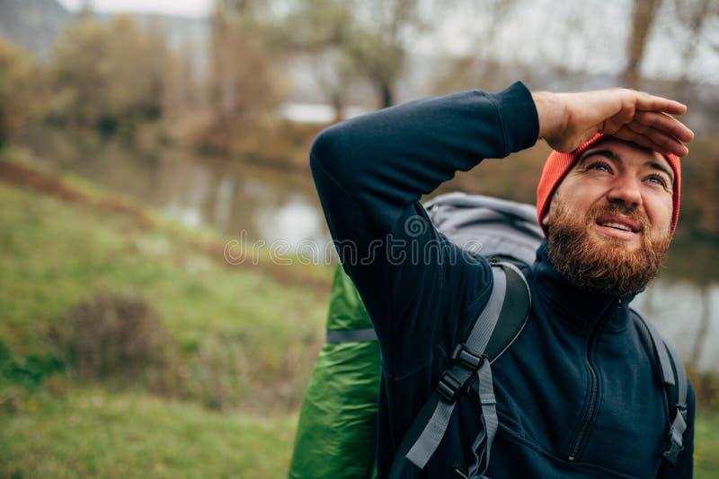 Junger Mann des Forschers, der in den Bergen mit dem Reiserucksack schaut zu einer schönen Ansicht mit der Hand auf der Stirn wan lizenzfreie stockfotografie