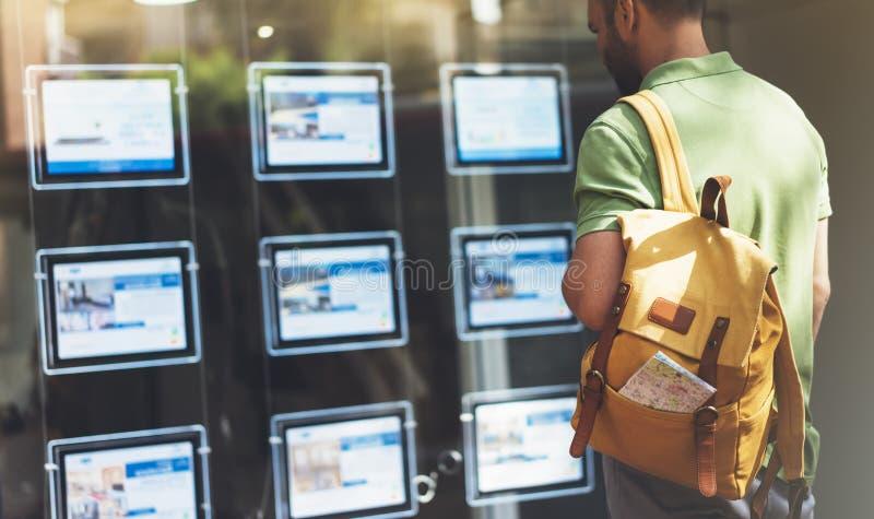 Junger Mann des Hippies mit Rucksack und die Karte, die Anzeige Promo-Plakathotel schaut, wählen Wohnungen Touristischer Reisendp stockfotos