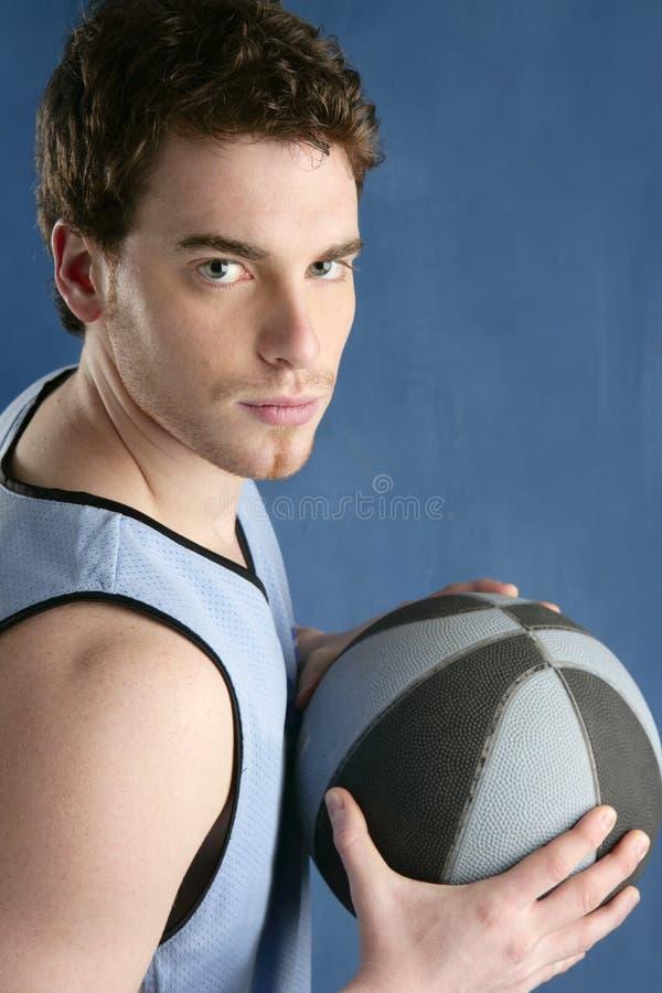 Junger Mann des Korbspielers über Blau stockfoto