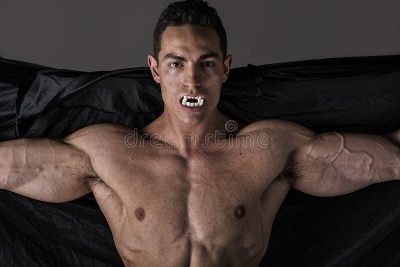 Junger Mann des nackten muskulösen Sitzes in den Memoranden, die als Vampir oder Dracula aufwerfen lizenzfreie stockfotografie