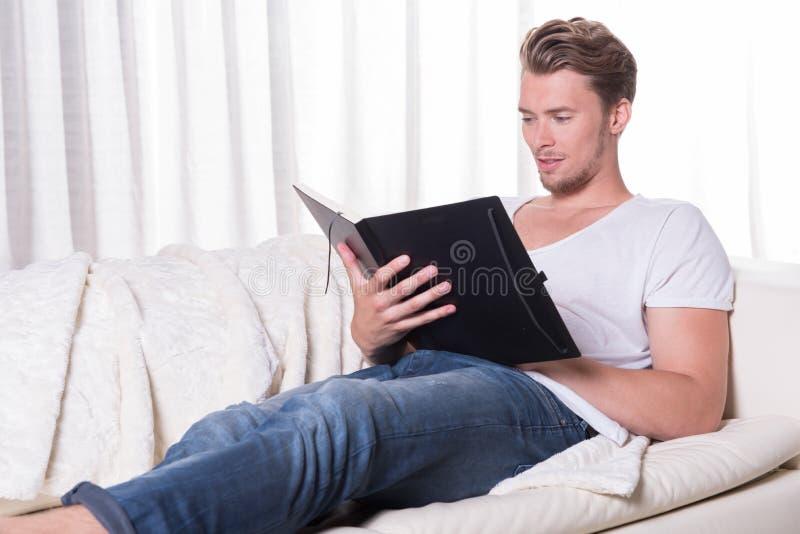Junger Mann des Porträts, der auf Couch sitzt und in einem Buch liest stockfotos