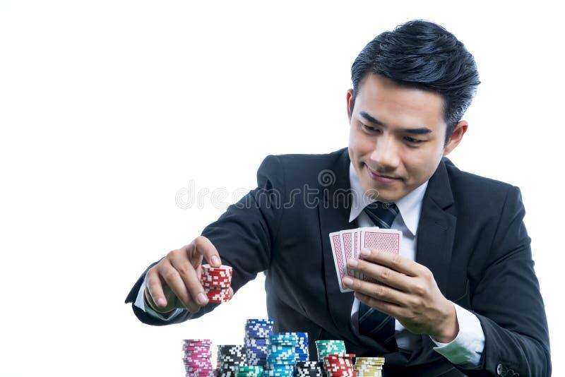 Junger Mann des Porträts im schwarzen Anzug setzt Stapel von Chips und von h lizenzfreies stockfoto