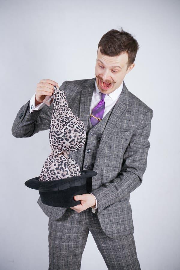 Junger Mann in einem Anzug zieht Leopard-BH von seinem Hut aus, aber er wünschte Tricks mit Wunder und Reichtum emotionaler Mann  stockfotografie