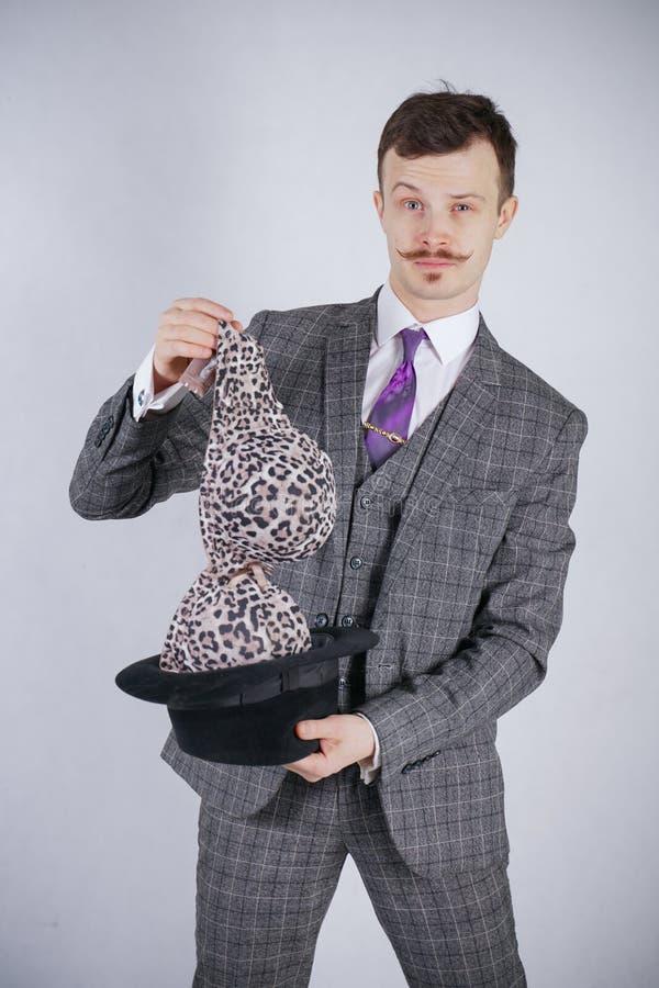 Junger Mann in einem Anzug zieht Leopard-BH von seinem Hut aus, aber er wünschte Tricks mit Wunder und Reichtum emotionaler Mann  stockbilder