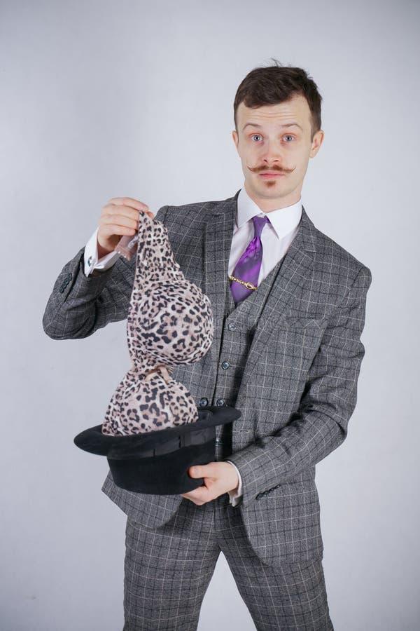 Junger Mann in einem Anzug zieht Leopard-BH von seinem Hut aus, aber er wünschte Tricks mit Wunder und Reichtum emotionaler Mann  stockfotos