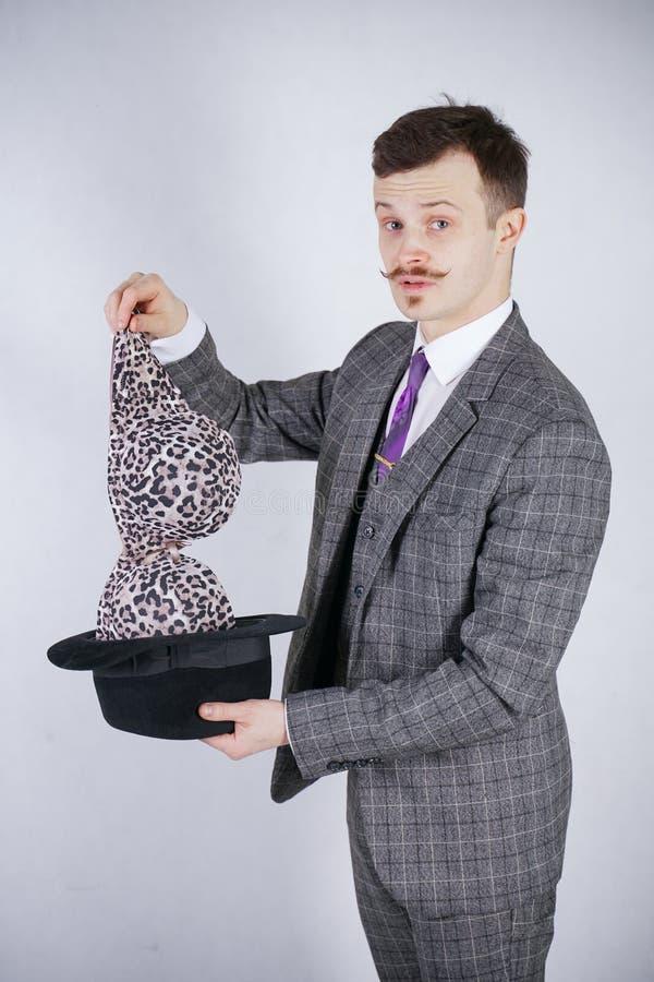 Junger Mann in einem Anzug zieht Leopard-BH von seinem Hut aus, aber er wünschte Tricks mit Wunder und Reichtum emotionaler Mann  lizenzfreies stockbild