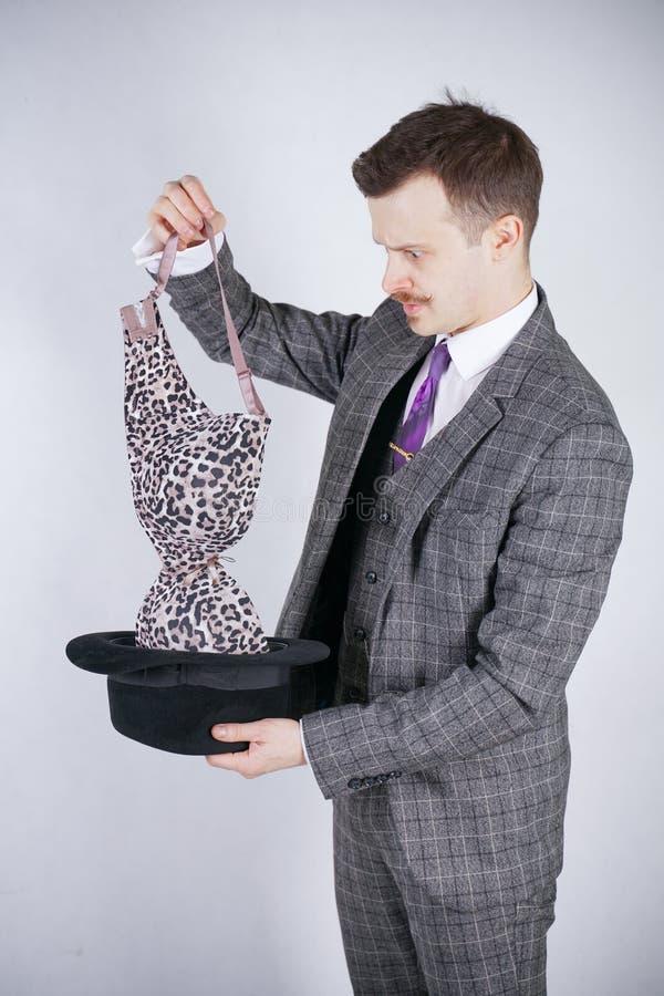 Junger Mann in einem Anzug zieht Leopard-BH von seinem Hut aus, aber er wünschte Tricks mit Wunder und Reichtum emotionaler Mann  lizenzfreie stockbilder