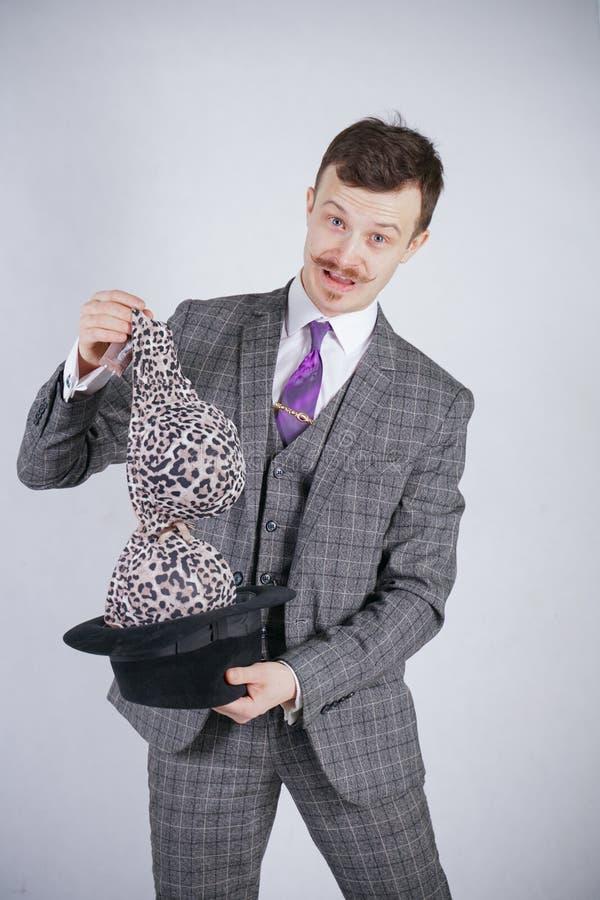Junger Mann in einem Anzug zieht Leopard-BH von seinem Hut aus, aber er wünschte Tricks mit Wunder und Reichtum emotionaler Mann  stockfoto