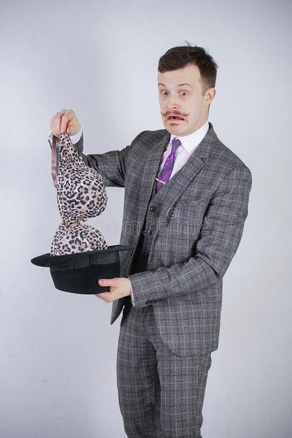 Junger Mann in einem Anzug zieht Leopard-BH von seinem Hut aus, aber er wünschte Tricks mit Wunder und Reichtum emotionaler Mann  lizenzfreie stockfotografie