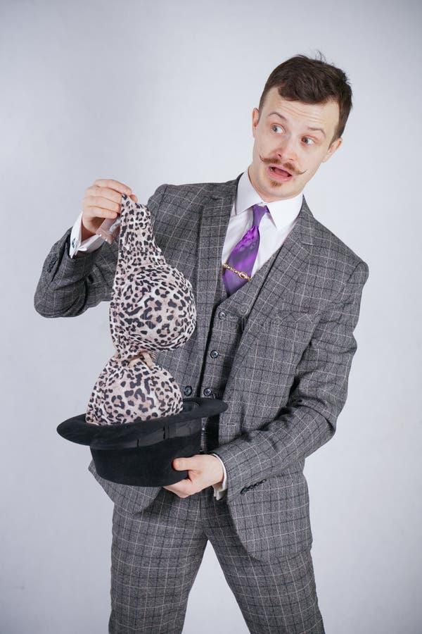 Junger Mann in einem Anzug zieht Leopard-BH von seinem Hut aus, aber er wünschte Tricks mit Wunder und Reichtum emotionaler Mann  lizenzfreie stockfotos